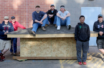 Students with finished roofing project